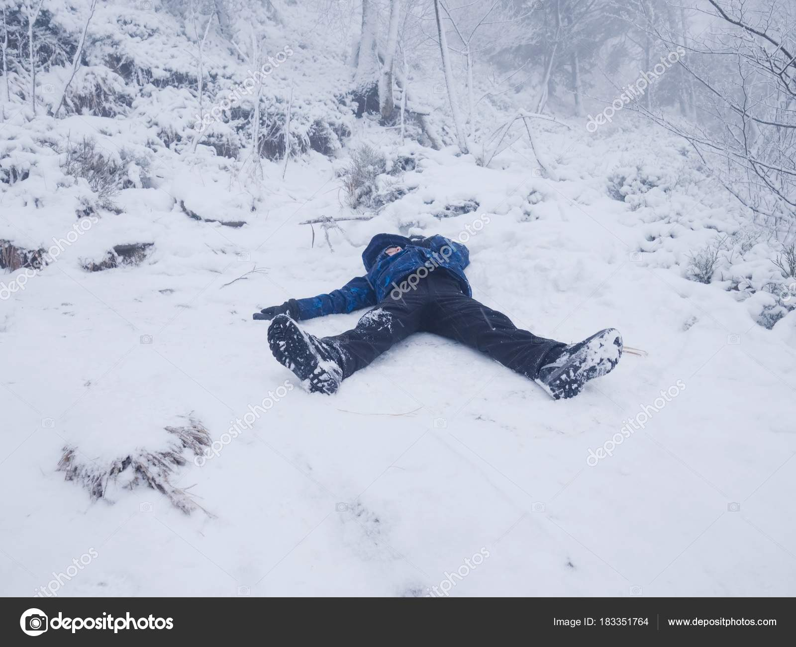 Funny Boy Laying In Snow And Makes An Angel With Spread Arms Kid Is