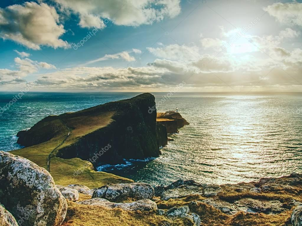 Famous look at Lighthouse on the cliff of Neist Point, rocky coast on the Isle of Skye