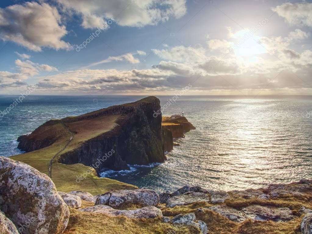 Neist Point lighthouse on rocky cliff above wavy sea. Blue evening sea and sharp cliffs,