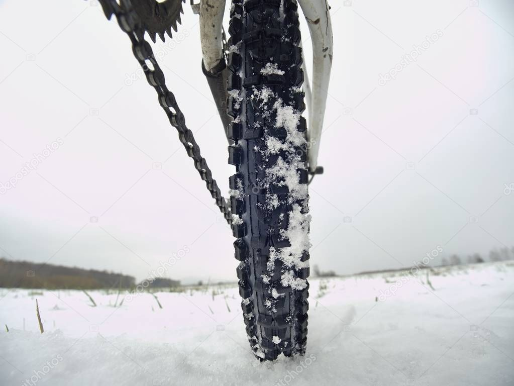 Low ankle photo of rear hweel of mtb in snowdrift. Picture taken within winter bike trip