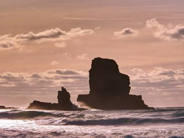 Amazing sunset, Talisker bay on the Isle of Skye in Scotland. Foamy sea, boulders and large cracked rocks with erosion marks. Rocky coastline with sea water