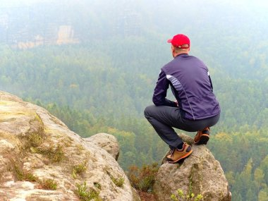 Man tourist hiker or trail runner looking at inspirational rocky  landscape