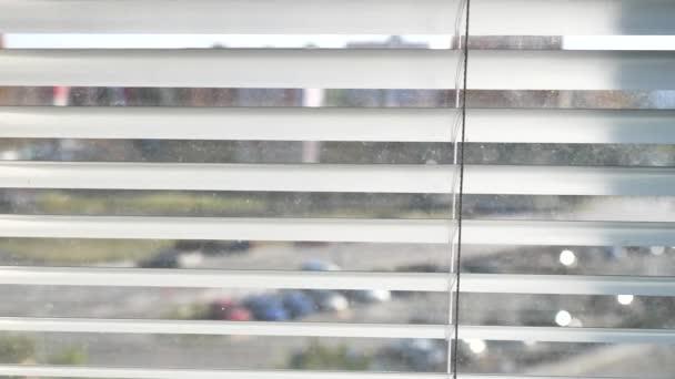 Pozorovat skrz plastové žaluzie na ulici. Zavřít ruku otevřít jalousie podívat se z okna.