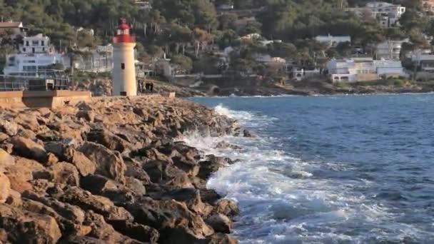 2020. január 28., Port Andratx, Mallorca, Spanyolország. A fiatalok a kőmólón sétálnak a régi világítótoronyig, hogy eredeti képeket készítsenek. Fehér hullámok csapódnak a mólóhoz..