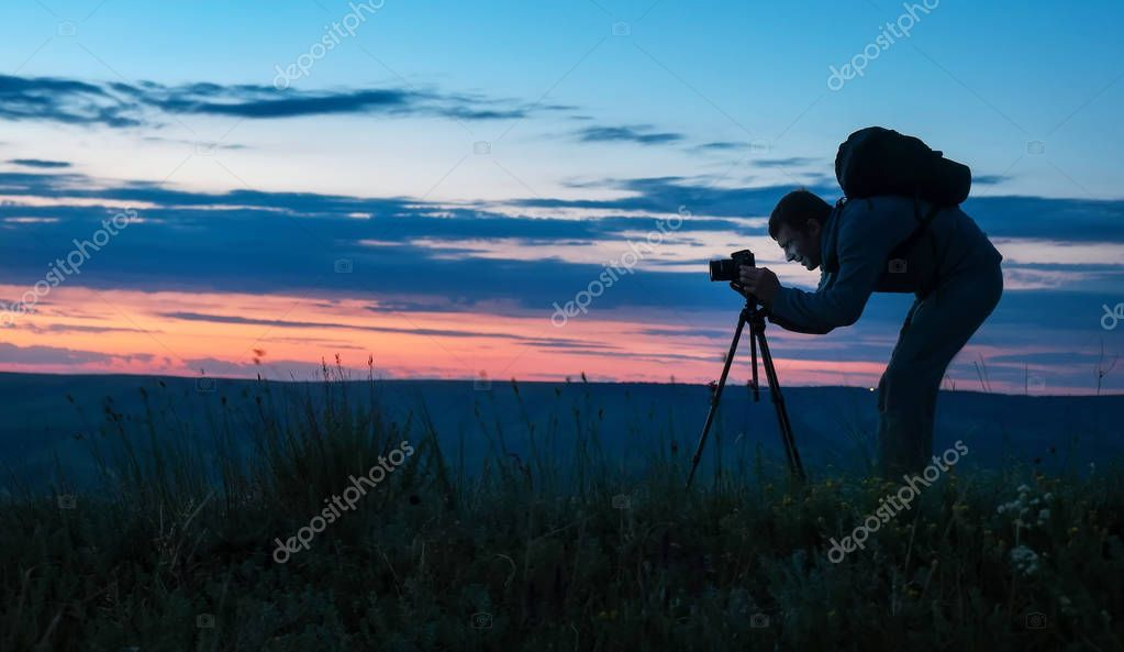 Silhouette of a professional photographer using a tripod, taking a photo