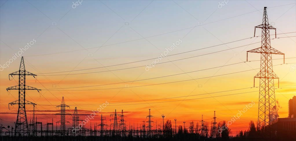 Electricity Pylons and Power Lines on sunset sky background