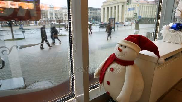 Vicces játék hóember néz ki a Cafe az utcára, és figyelte a járókelők