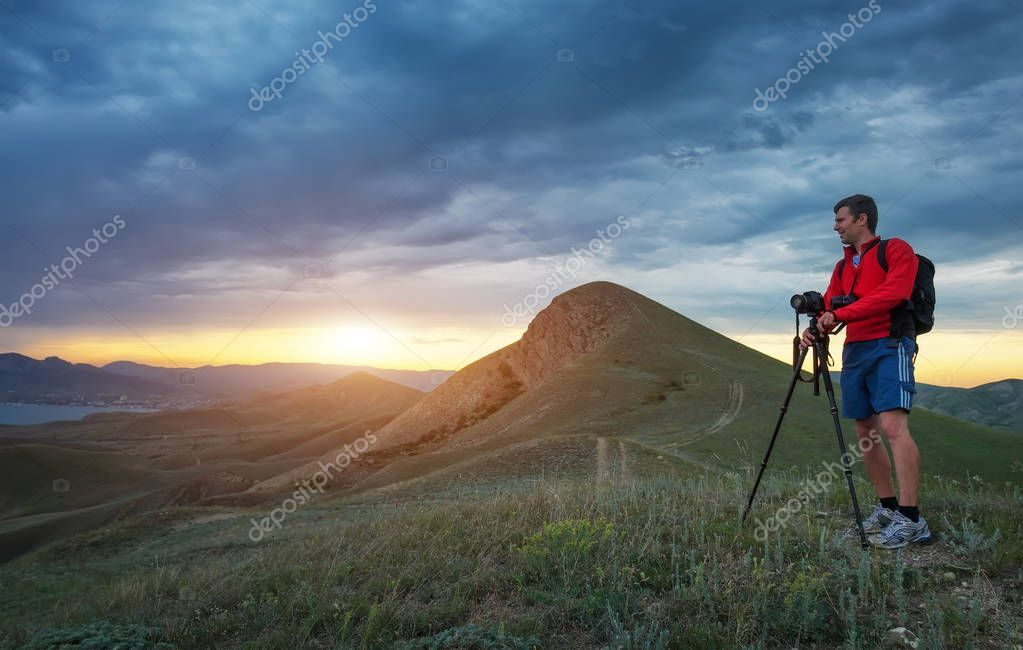 Professional photographer using a tripod, taking a photo of a mountain
