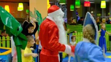 Energodar, Ukraine - 29 December 2017: Children celebrate Christmas and new year having fun dancing with Santa Claus at the presentation near the Christmas tree in kindergarten