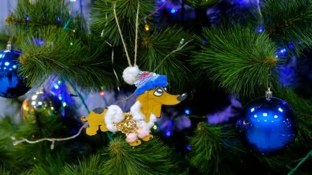 Nový rok strom s hračkami. Hračka ve tvaru psa na vánoční stromeček s míčky a girlandy