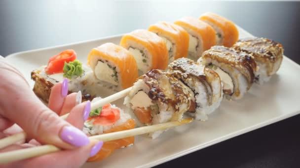 ruka drží bambusové tyčinky a posouvá sushi na bílém talíři.