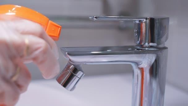 Egy tisztítószer spray közelsége egy króm csapon a fürdőszobában. Higiénia, háztakarítás, fertőtlenítés a koronavírustól. lassított felvétel
