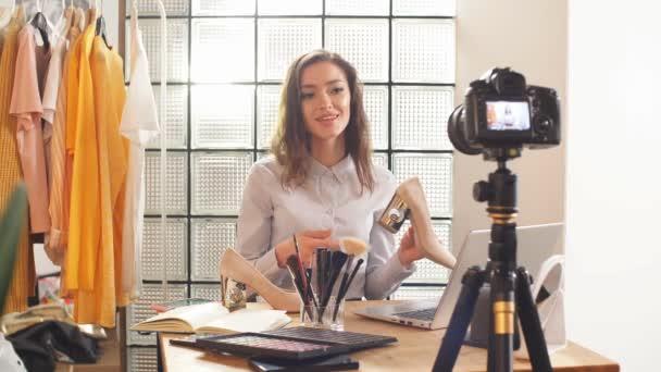 Bei der Online-Übertragung einer Beauty-Bloggerin zu Hause versucht das Mädchen extrem ehrlich zu ihren Abonnenten zu sein. Darstellung von Schuhen auf der Kamera. Fernbedienung