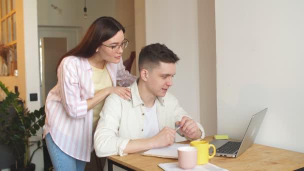 Mladý veselý pár spravuje finance, přezkoumává jejich bankovní účty.
