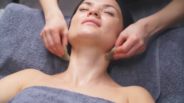 Kaukasische Dame bekommt eine Facelift-Massage in einem Schönheitssalon. das Konzept der Gesichtspflege