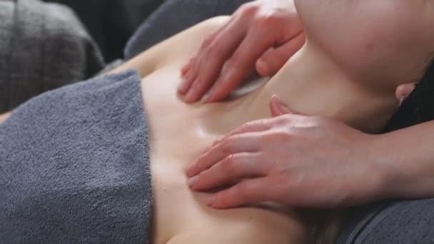Atraktivní žena leží na posteli v salonu krásy a dostane masáž na dekoltu a krku límec oblasti