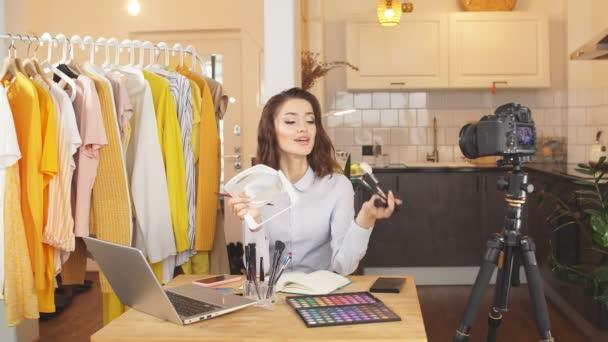 mladá žena blogger dělá make-up na kameru, ukazuje její denní make-up pro předplatitele, vzdálená práce doma