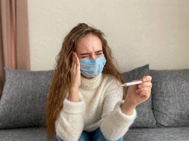 girl in a disposable medical mask is sitting at home with a headache. The girl has a high temperature
