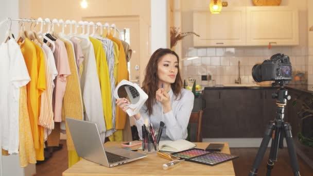 Roztomilý žena blogger dělá make-up na kameru, ukazuje její denní make-up pro následovníky. blogger nahrává video na profesionální fotoaparát