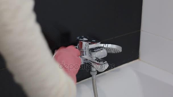 Frau wäscht Ausstattung des Bades in Bad