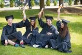oktatás, érettségi és emberek koncepció - csoport boldog nemzetközi diák habarcs táblák és főiskolai oklevelek ruhák