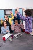 Portrét skupiny po spuštění kreativních lidí, kteří mají schůzku s přenosným počítačem v moderní kanceláři. Podnikatelé mají uvolněné konverzaci nad nový projekt v ucastnin