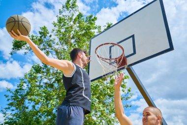Couple of guys playing basketball outside
