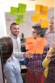 mladí kreativní spuštění lidi na schůzi v moderní kancelářské dělat plány a projekty s post samolepky na sklo