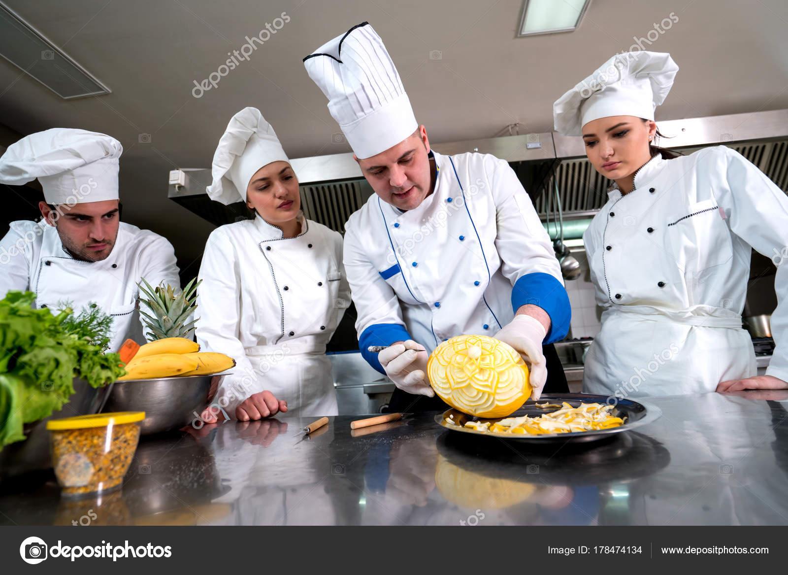 Attractive Chef Cocina Con Jóvenes Aprendices Enseñar Hacer Cesta Frutas Decorativasu2013  Imagen De Archivo