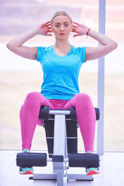 Attractive fit woman working out abs in fitness gym, making ab intervals