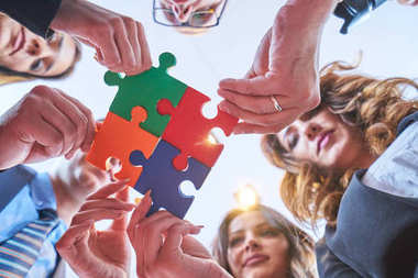 Group of business people assembling jigsaw puzzle and represent team support and help concept in modern office