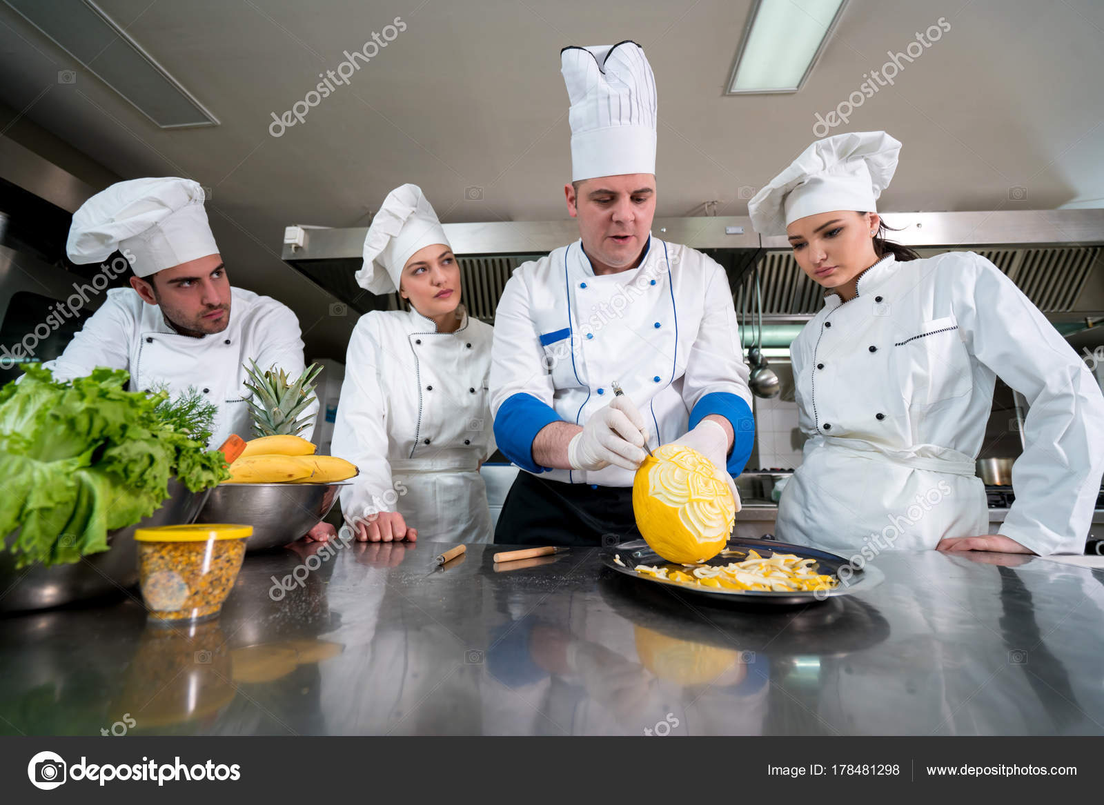 Kitchen chef young apprentices teaching make decorative fruit basket stock photo