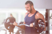 Photo sport, bodybuilding, lifestyle and people concept - young man with barbell flexing muscles and making shoulder press lunge in gym
