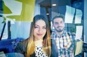 podnikání, spouštění, plánování, řízení a lidé koncept - šťastný tvůrčí tým psaní na samolepky na skleněné desky v moderní kanceláři úřadu