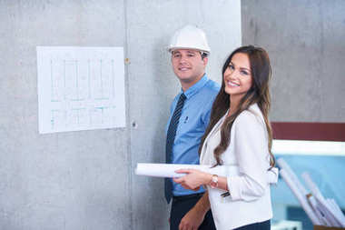Business people group on meeting with construction engineer architect looking building blueprint in modern office