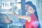 üzleti, indítás, tervezés, vezetés és emberek koncepció - boldog kreatív csapat írás office üveg Board matricák