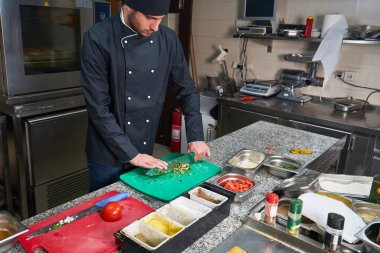 Chef sprinkling spices on dish in commercial kitchen