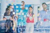 podnikání, spouštění, plánování, řízení a lidé koncept - šťastný tvůrčí tým psaní na samolepky v kanceláři skleněná deska