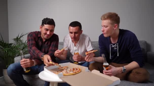 Three cheerful young guys eating pizza taking it from table.
