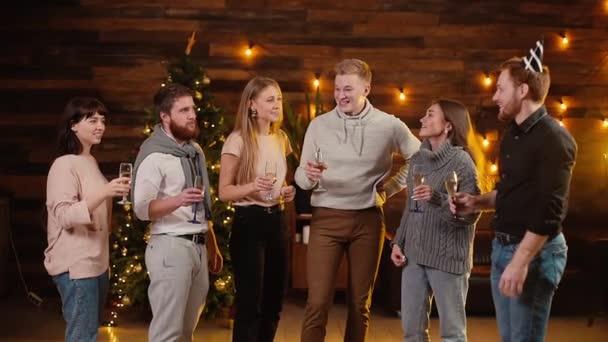Veselí přátelé cinkají sklenicemi šampaňského a oslavují Nový rok