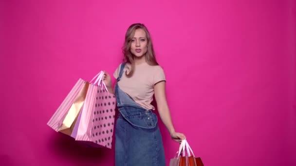 Veselý mladá žena tanec při držení barevné nákupní tašky