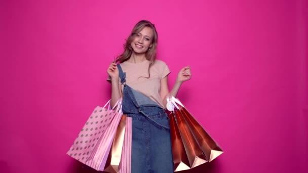 Usmívající se mladá žena v džínových šatech držící kreditní kartu a nákupní tašky