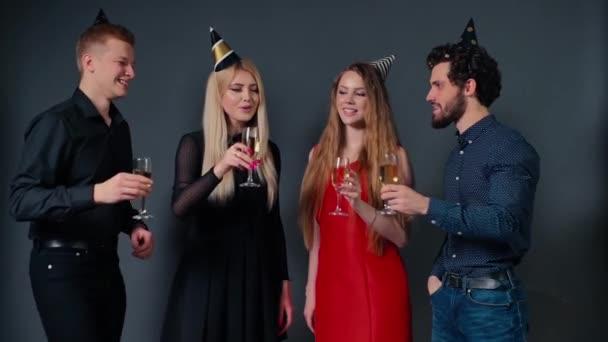 Négy gyönyörű és vidám barát csörömpöli poharát pezsgővel.