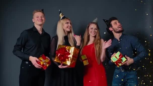 Egy csapat boldog ember táncol ünnepi ajándékdobozokkal a kezében.