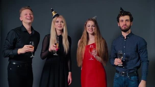 Két vonzó srác és két gyönyörű lány csörömpöl pezsgős poharakkal.