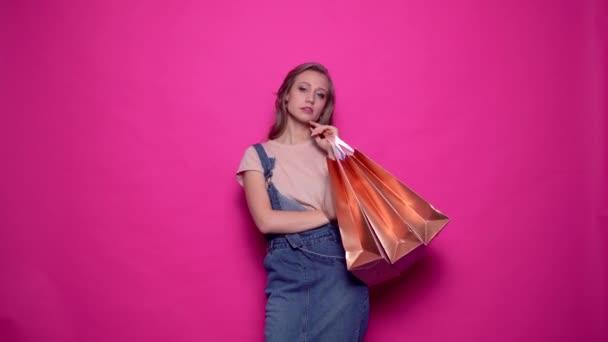 Atraktivní mladá žena se dívá do kamery, zatímco drží zlaté papírové tašky