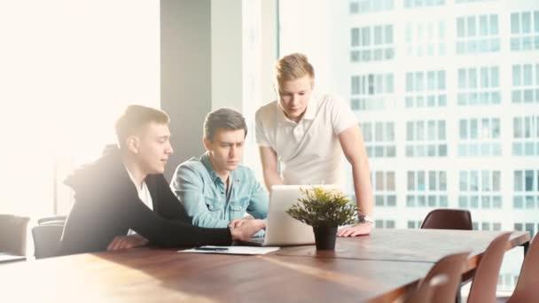 Barátságos kreatív kollégák csapat megvitatják a projektet egy laptop