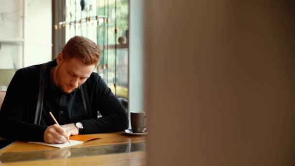 Portrait of young man is sitting in cafe and making entries in his notepad