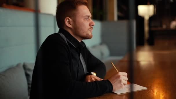 Young beautiful man sits in a cafe and writes into a notebook