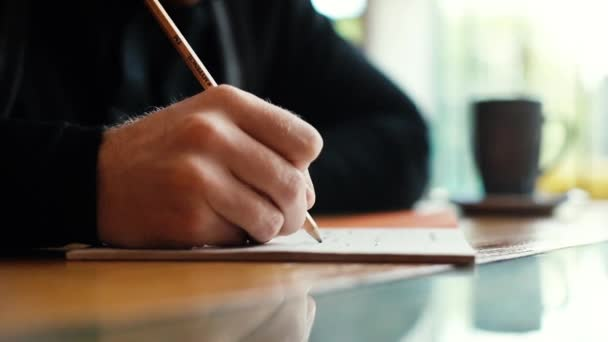 Hand of man writes text by pen on paper close-up in slow motion
